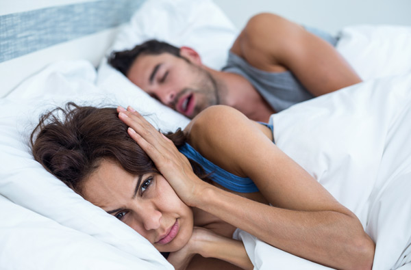 Woman covering ears while husband snores.