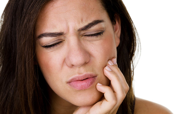 Woman holding jaw due to TMJ pain.